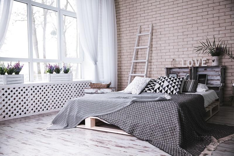 podwójne łóżko na tle ściany z jasną cegłą